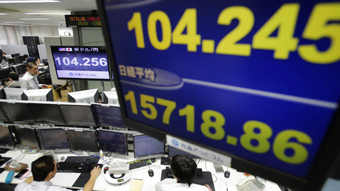 Money traders work under a screen indicating update of U.S. dollars against yen at a foreign exchange brokerage in Tokyo, Wednesday, Jan. 15, 2014. The euro was up 0.2 percent at $1.364 while the dollar rose 0.2 percent to 104.33 yen. (AP Photo/Shizuo Kambayashi)