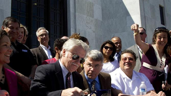 Oregon Gov. John Kitzhaber signs Senate Bill 833 into law on the steps of the State Capitol in Salem, Ore. on Wednesday,  May 1,  2013. The bill authorizes driver's cards for those without the documents to obtain regular driver's licenses. (AP Photo/The Oregonian, Beth Nakamura)