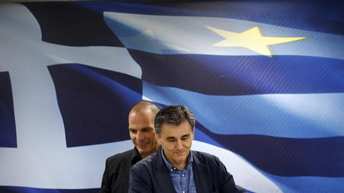 Newly-appointed Finance Minister Euclid Tsakalotos and outgoing Yanis Varoufakis arrive before handover ceremony in Athens