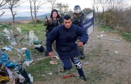 A migrant tries to escape from Macedonian police officers as he tries to cross the Greek-Macedonian border near the Greek village of Idomeni