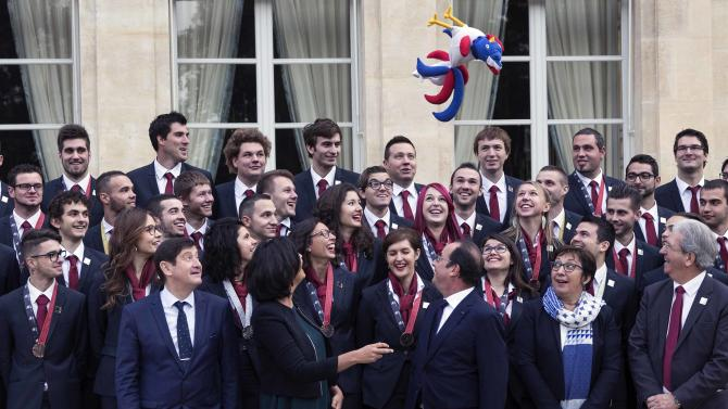 A stuffed rooster doll is thrown in the air as French President Hollande and the decorated challengers of the 43rd WorldSkills pose for a family picture after a ceremony at the Elysee Palace in Paris