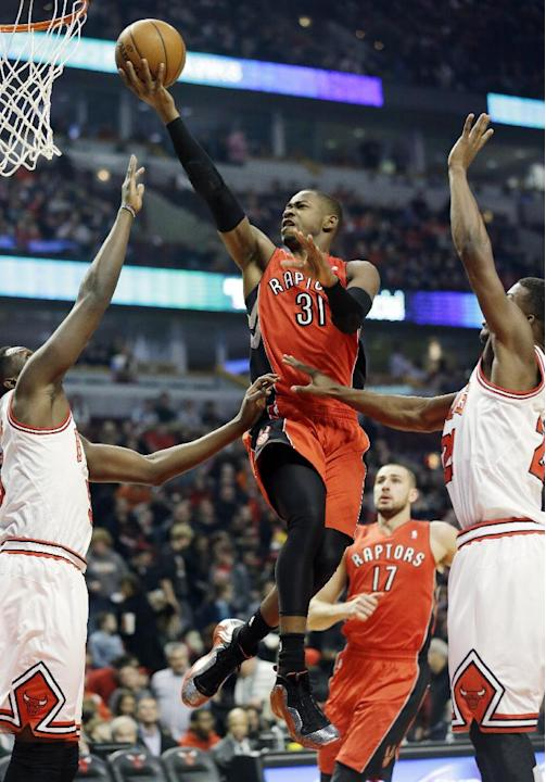 Toronto Raptors guard Terrence Ross (31) drives to the basket as Chicago Bulls forward Luol Deng, left, and guard Jimmy Butler defend during the first half of an NBA basketball game in Chicago on Satu