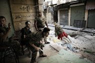 "<p>Free Syrian Army fighters man a position in the Old City of Aleppo. Serious human rights violations have soared dramatically in Syria, a top UN investigator said Monday, calling for ""appropriate action"" against perpetrators of atrocities in the wartorn country.</p>"