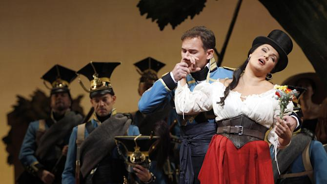 """In this Sept. 20, 2012 photo, Mariusz Kwiecien performs as sergeant Belcore alongside Anna Netrebko performing as Adina during the final dress rehearsal of Gaetano Donizetti's """"L'Elisir d'Amore"""" at the Metropolitan Opera in New York. That most endearing of all comedies, Donizetti's """"L'Elisir d'Amore,"""" opened the Metropolitan Opera season on Monday, Sept. 24 in a modest new production made memorable by an outstanding cast. (AP Photo/Mary Altaffer)"""