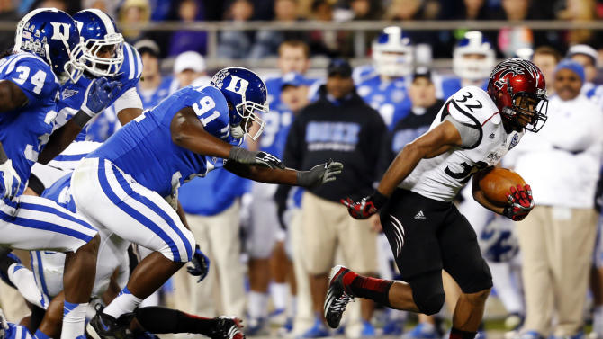 Cincinnati's Pat O'Donnell (34) runs past Duke's Jamal Bruce (91) and Jonathan Woodruff (34) during the first half of the Belk Bowl NCAA college football game in Charlotte, N.C., Thursday, Dec. 27, 2012. (AP Photo/Chuck Burton)