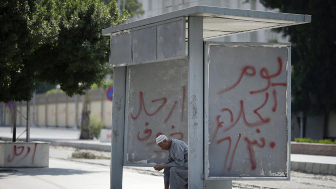 """An Egyptian man waits at train stop in front of the presidential palace, days ahead of planned protests against the country's Islamist President Mohammed Morsi in Cairo, Egypt, Friday, June 28, 2013. Arabic reads, """"leave, left, evacuation day.""""(AP Photo/Hassan Ammar)"""