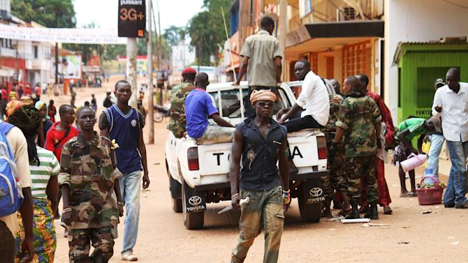 A rebel soldier without a uniform and carrying only a knife walks past other rebel soldiers and civilians in central Bangui, capital of the Central African Republic, Wednesday, March 27, 2013. Aid groups and the international community on Tuesday condemned widespread looting in Central African Republic's capital, saying that even hospitals had been robbed in the aftermath of a weekend coup that ousted the president of a decade. Efforts to restore order to Bangui, a city of 700,000, came as a rebel leader declared himself the new president and announced he would stay in power for three years. (AP Photo)
