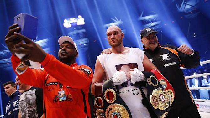 Tyson Fury celebrates winning the fight with trainer and father Peter Fury (R)