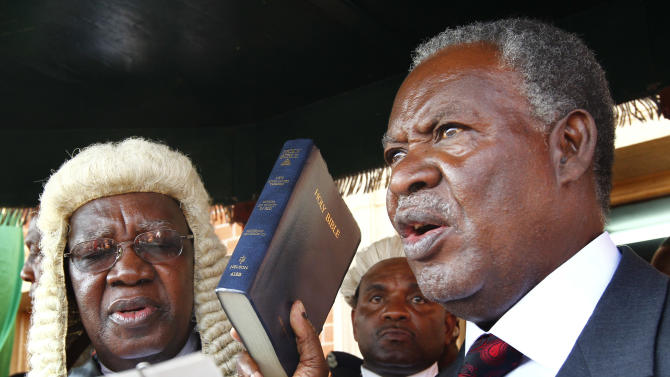 """Zambia's new President Michael Sata, right, takes the oath of office on the steps of the supreme court in Lusaka, Zambia, Friday Sept. 23, 2011. Sata defeated  incumbent Zambia's President Rupiah Banda in Tuesday Sept. 20 elections. The man who once threatened to expel """"bogus"""" Chinese investors became Zambia's new president Friday on the back of a campaign that promised jobs and education, and played down the anti-China rhetoric that had failed to win him traction in three previous elections. (AP Photo/Jerome Delay)"""