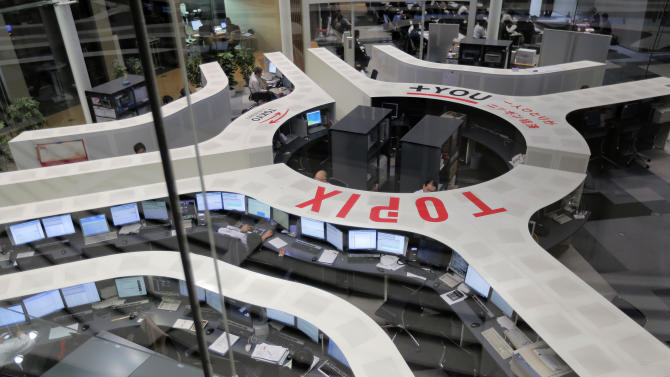 Tokyo Stock Exchange employees work at the computer terminal in Tokyo, Wednesday, May 22, 2013. Asian stock markets were mostly higher Wednesday after investor confidence was boosted by a Federal Reserve official's comments that the U.S. central bank should stick with its super-easy monetary policy. (AP Photo/Itsuo Inouye)
