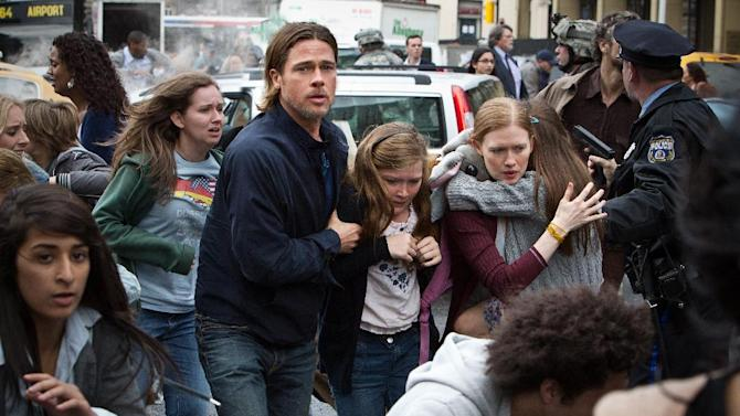 """This publicity image released by Paramount Pictures shows, from center left, Brad Pitt as Gerry Lane, Abigail Hargrove as Rachel Lane, and Mireille Enos as Karin Lanein a scene from """"World War Z."""" In a small-scale marketing experiment, for $50, some fans got to see Brad Pitt's hotly anticipated zombie thriller """"World War Z"""" before all their friends. They also got 3D glasses to keep, popcorn, a poster, and a promised copy of the DVD when it comes out. (AP Photo/Paramount Pictures, Jaap Buitendijk)"""