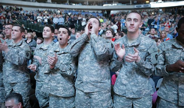 U.S. soldiers cheer from the front row before an NBA basketball game between the Milwaukee Bucks and Dallas Mavericks, Saturday, Dec. 14, 2013, in Dallas. Season ticket holders donated their front row
