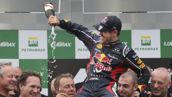 Red Bull driver Sebastian Vettel of Germany, top, sprays champagne on his teammates after the Brazil's Formula One Grand Prix at the Interlagos race track in Sao Paulo, Brazil,  Sunday, Nov. 25, 2012. Vettel overcame a first-lap crash to clinch his third straight Formula One championship title on Sunday, finishing sixth in an incident-filled Brazilian Grand Prix won by Jenson Button under pouring rain.(AP Photo/Andre Penner)