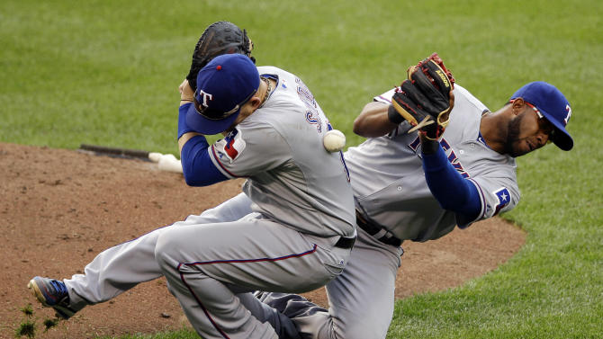 Texas Rangers first baseman Brandon Snyder, left, and shortstop Elvis Andrus collide as they drop a pop fly by Baltimore Orioles' Robert Andino in the seventh inning of the first baseball game of a doubleheader in Baltimore, Thursday, May 10, 2012. Baltimore won 6-5. (AP Photo/Patrick Semansky)