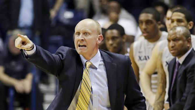 Xavier head coach Chris Mack gestures to his players in the second half of their 64-62 win over Memphis in an NCAA college basketball game, Tuesday, Feb. 26, 2013, in Cincinnati. (AP Photo/Al Behrman)