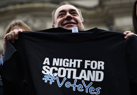 "Scotland's First Minister Alex Salmond  holds a t-shirt promoting a concert being held in support of a ""Yes"" vote, in Edinburgh"