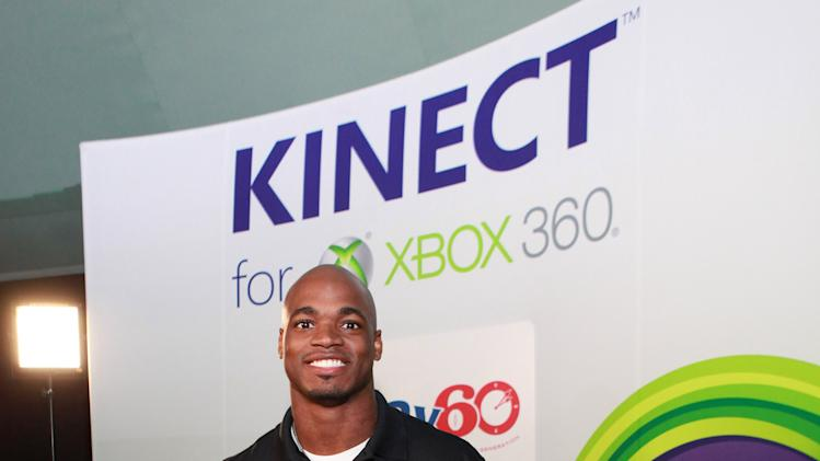 Young Zoe Stein, NFL running back Adrian Peterson and Duke Stein at Kinect for Xbox 360, on Thursday, Jan. 31, 2013 in New Orleans, LA. (Photo by Barry Brecheisen/Invision for Xbox/AP Images)