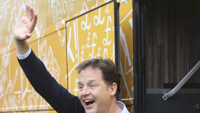 Leader of the Liberal Democrat party Nick Clegg waves to young children as he leaves the Westerton nursery after a campaign event in Glasgow