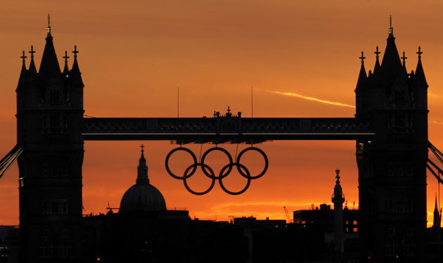 The sun sets behind the Tower Bridge with a display of Olympic rings, on Saturday, July 21, 2012, in London. The 2012 London Olympics opens Friday, July 27. (AP Photo/Charlie Riedel)