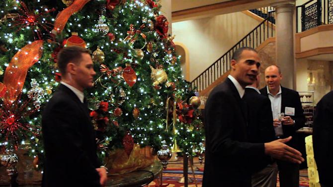 "In this image from video, President Barack Obama lookalike Larry Graves greets people during an appearance. Graves has the security detail, the prominent ears and the U.S. flag pin, but substitute teacher Graves is no Barack Obama. He's a professional lookalike for the president. They have something else in common, too: a frantic schedule leading up to the inauguration. ""It's definitely a busy time,""  Graves said. ""Between the campaign season and the inauguration, it's been prime time. Barack Obama is a respectable guy. People want to have him at their parties."" (AP Photo)"