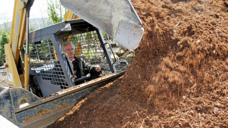 "In this May 17, 2012 photo, Richard Lowe loads a truck with mulch in Morrisville, Vt. Nursery owners and landscapers around Vermont have been getting big bills from the state recently for unpaid sales taxes on products like bark mulch and soil additives that many thought had an agricultural exemption from the 6 percent levy. Some are complaining that they were caught unaware of a change in the tax code made six years ago. ""You don't just change the taxes and laws and not tell somebody,"" said Lowe, owner of Green Mountain Landscaping in Morrisville, who is fighting $18,000 in bills for back taxes. (AP Photo/Toby Talbot)"