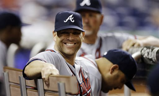 Atlanta Braves' Tim Hudson sits in the dugout smiling during the ninth inning of a baseball game against the Miami Marlins in Miami, Tuesday, April 9, 2013. The Braves won 3-2