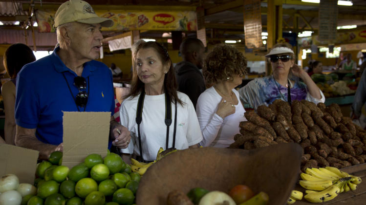 """In this Jan. 23, 2014 photo, tourists traveling with the """"people-to-people"""" program make a purchase in a Cuban agricultural market in Havana, Cuba. Tour operators insist they're supporting local organic farmers, performers, artists, musicians and entrepreneurs who run private restaurants, adding that the Cuban government's involvement in scheduling is minimal and agendas carefully comply with U.S. rules barring sun-and-sand tourism. (AP Photo/Ramon Espinosa)"""