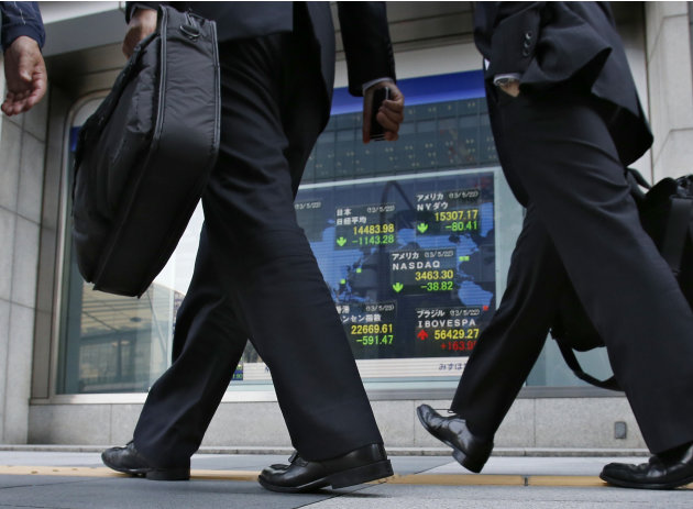 People walk by an electronic stock indicator outside a securities firm in Tokyo, Thursday, May 23, 2013. Japanese stocks plummeted Thursday after a spike in government bond yields and unexpectedly wea
