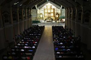 Typhoon Haiyan survivors take part in a nine-day Christmas vigil mass at a damaged church in Palo