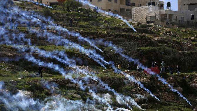 Palestinian protesters run away from tear gas fired by Israeli troops during clashes near Israel's Ofer Prison, near the West Bank city of Ramallah