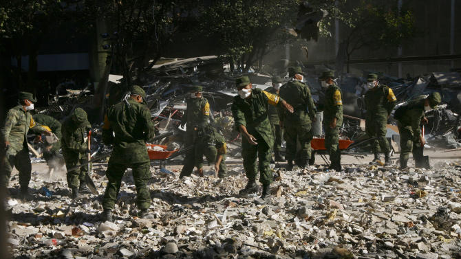 Soldiers remove debris after an explosion at the state-owned oil company PEMEX office complex in Mexico City, Sunday Feb. 3, 2013. Mexico's state-owned oil company says rescuers have found another body amid the rubble of a headquarters building damaged by a still-unexplained blast. The find raises the death toll of Thursday's explosion to about 34 people. (AP Photo/Marco Ugarte)