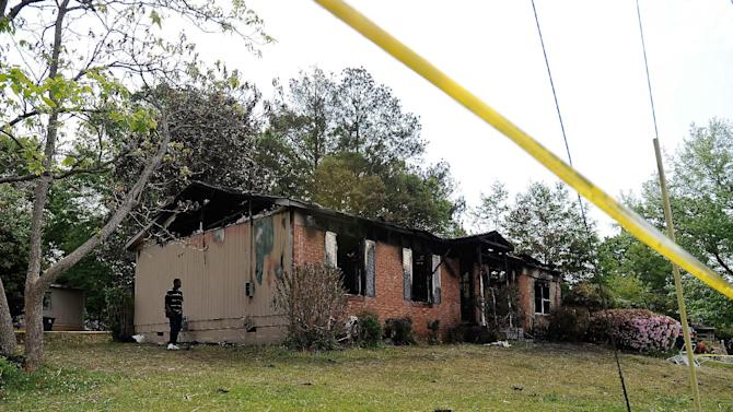 A neighbor walks past the side of a charred single-story house after a fatal fire killed five, including four children, in Newnan, Ga., Saturday, April 27, 2013. The fire killed Alonna T. McCrary, 27, as well as her 5-year-old daughter Eriel McCrary and 2-year-old daughter Nikia White, according to Glenn Allen, the Georgia state Insurance commissioner's spokesman. Two other children, Messiah White, 3, and McKenzie Florence, 2, also died. Allen said the two were sleeping over at the home. A fifth child, 11-year-old Nautica McCrary, escaped the burning home and was taken to a hospital to be treated for smoke inhalation. (AP Photo/David Tulis)
