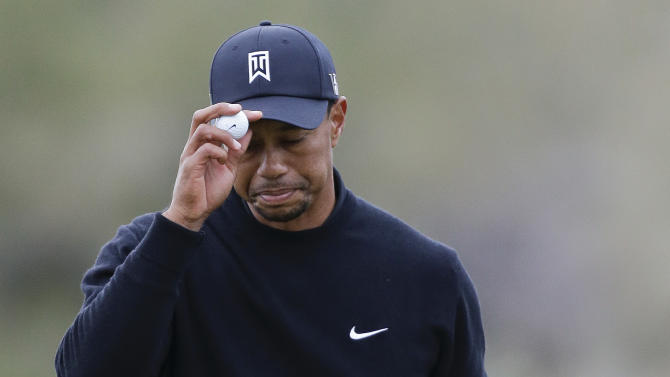 Tiger Woods tips his hat to fans after putting on the 11th green in the first round against Charles Howell III during the Match Play Championship golf tournament, Thursday, Feb. 21, 2013, in Marana, Ariz. (AP Photo/Ted S. Warren)