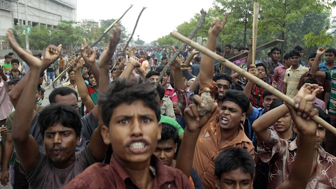 Bangladeshi garment workers shout slogans and block a road during a protest against the collapse of an eight-story building that housed several garment factories and poor safety standards, in Dhaka, Bangladesh, Saturday, April 27, 2013. Police in Bangladesh took into custody five people in connection with the collapse of a shoddily-constructed building that collapsed this week, as rescue workers pulled out 19 survivors out of the rubble on Saturday and vowed to continue as long as necessary to find others despite fading hopes. (AP Photo/A.M. Ahad)