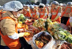 Volunteers are seen making kimchi, a traditional Korean…
