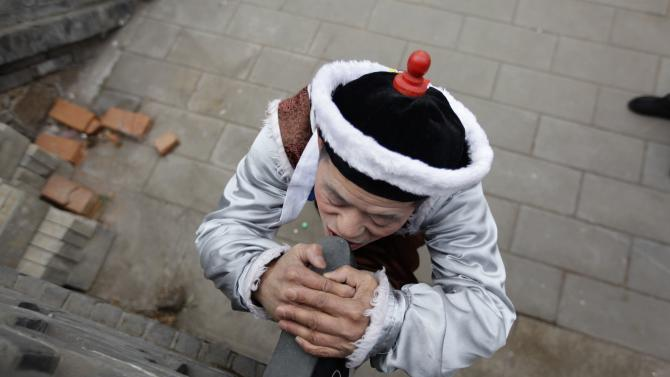 A folk artist stretches as he waits for a performance in Beijing