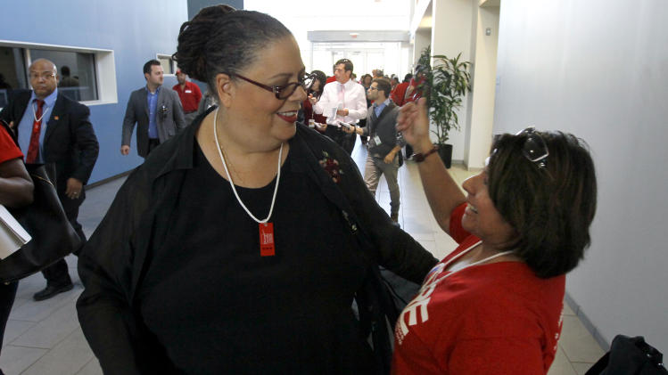 "Karen Lewis, president of the Chicago teachers union, left, is greeted by a union member after her meeting with the union's House of Delegates Friday, Sept. 14, 2012, in Chicago. Lewis told the delegates that a ""framework"" was in place to end the teachers strike. (AP Photo/Charles Rex Arbogast)"