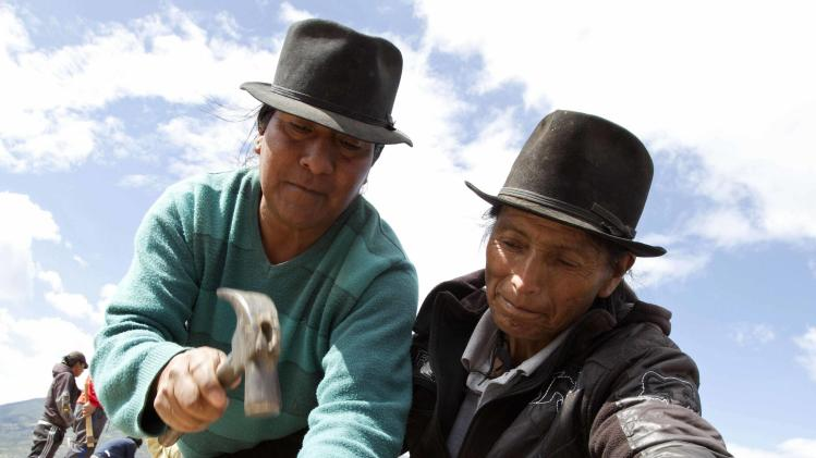 Ecuadorean indigenous indians build the roof of a house in Otavalo