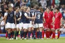 Players from the U.S. and North Korea teams shake hands with each other after their women's football first round Group G match at Old Trafford in Manchester during the London 2012 Olympic Games