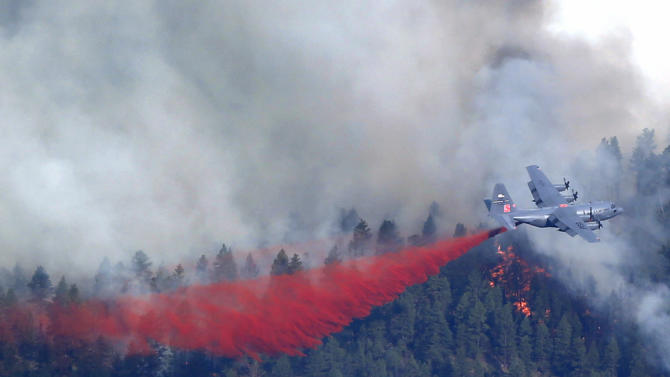 A military C-130 drops a load of fire retardant on a wildfire near Pine, Colo., on Wednesday, June 19, 2013. A new wildfire in the foothills southwest of Denver forced the evacuation of dozens of homes Wednesday as hot and windy conditions in much of Colorado and elsewhere in the West made it easy for fires to start and spread.  (AP Photo/Ed Andrieski)
