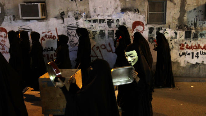 """Bahraini protesters bang on pans and use compressed air horns to sound out anti-government slogans in Sanabis, Bahrain, Tuesday, March 12, 2013. Riot police stormed the protest, firing tear gas and making arrests. Protesters in opposition strongholds nationwide held similar noisy rallies Tuesday night, banging on drums, metal trays and pot lids to stir support for a planned """"Dignity Strike"""" on Thursday _ when government opponents refrain from going to work, school or shopping and close their stores. Graffiti on the wall includes images of jailed political leaders and reads: """"God avenge us,"""" """"Dignity Strike 2, our date is March 14,"""" and """"God is greater."""" (AP Photo/Hasan Jamali)"""