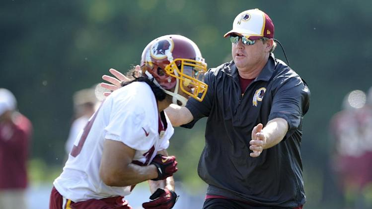 In this June 17, 2014 file photo, Washington Redskins head coach Jay Gruden takes part in a drill with running back Roy Helu, Jr., left, during an NFL football minicamp in Ashburn, Va. After years of waiting for his turn, and after months of meticulous planning, Jay Gruden begins his first NFL training camp as a head coach as the Redskins report to their facilities in Richmond, Va