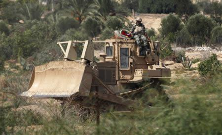 Egyptian soldier sits atop a bulldozer on the border between Egypt and southern Gaza Strip