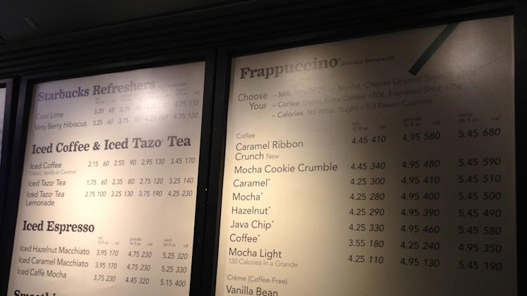 In this Monday, June 17, 2013 photo, a menu board showing calorie counts hangs at a Starbucks in New York. The Seattle-based coffee chain says it will start posting calorie counts on menu boards nationwide next week, ahead of a federal regulation that would require it to do so. (AP Photo/Candice Choi)