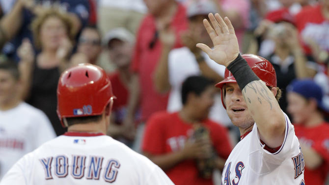 Texas Rangers' Michael Young is congratulated by Josh Hamilton, right, following Young's two-run home run that scored Hamilton off a pitch from Minnesota Twins' Nick Blackburn in the first inning of a baseball game, Monday, July 25, 2011, in Arlington, Texas. (AP Photo/Tony Gutierrez)