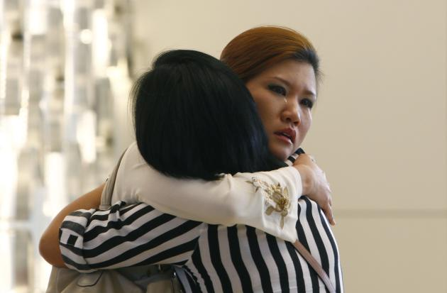 Relatives of a passenger onboard the missing Malaysia Airlines flight MH370 cry inside a hotel they are staying, in Putrajaya