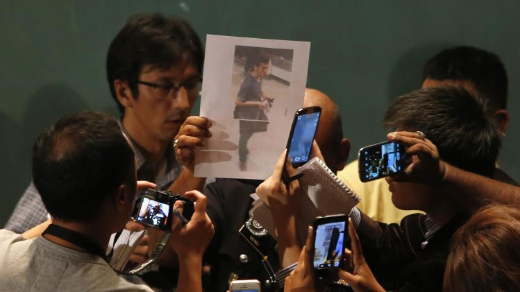 A journalist holds up a photo of one of the two men whom the Malaysian police believe were travelling onboard the missing Malaysia Airlines MH370 on stolen passports after a news conference at Kuala Lumpur International Airport