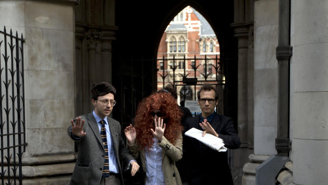 A woman dressed up in a wig to look like Rebecca Brooks, center, the former Chief Executive Officer of News International pretends to be her arriving with two men at the Leveson media ethics inquiry, at the High Court in London, Friday, May 11, 2012.  (AP Photo/Matt Dunham)
