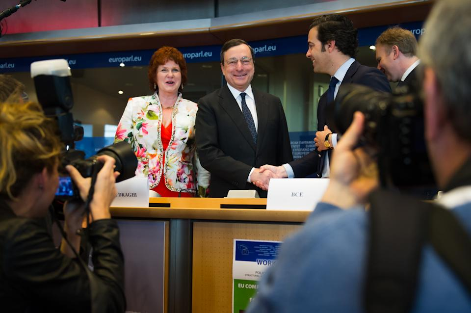 European Central Bank President Mario Draghi, center, smiles as he arrives to address the committee on economic and monetary affairs at the European parliament in Brussels, Wednesday April 25, 2012. (AP Photo/Geert Vanden Wijngaert)