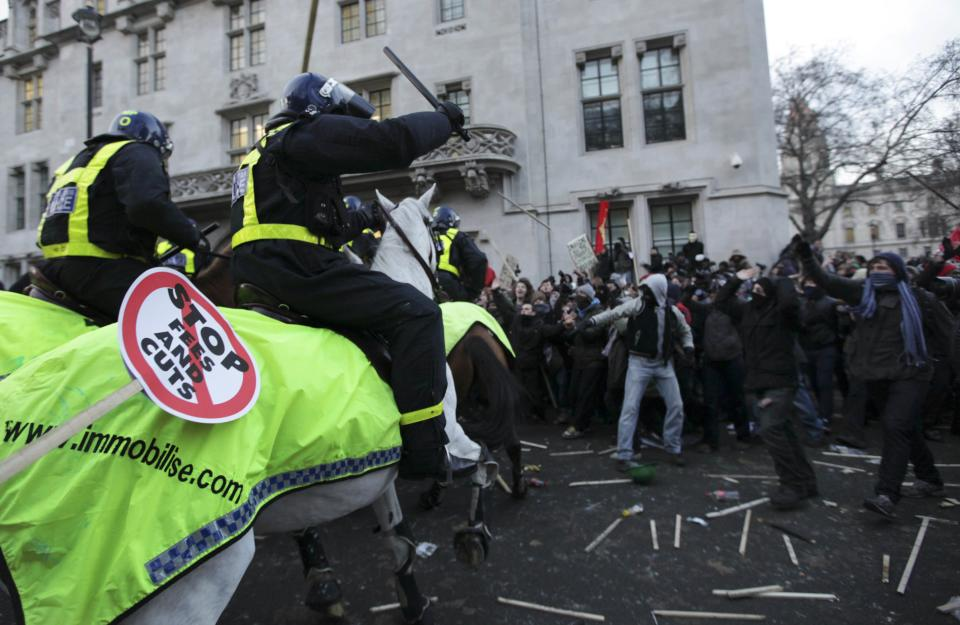 Protesters and police officers on horseback clash during a protest against an increase in tuition fees on the edge of Parliament Square in London, Thursday, Dec. 9, 2010.  Police clashed with protesters marching to London's Parliament Square as lawmakers debated a controversial plan to triple university tuition fees in England.  (AP Photo/Matt Dunham)